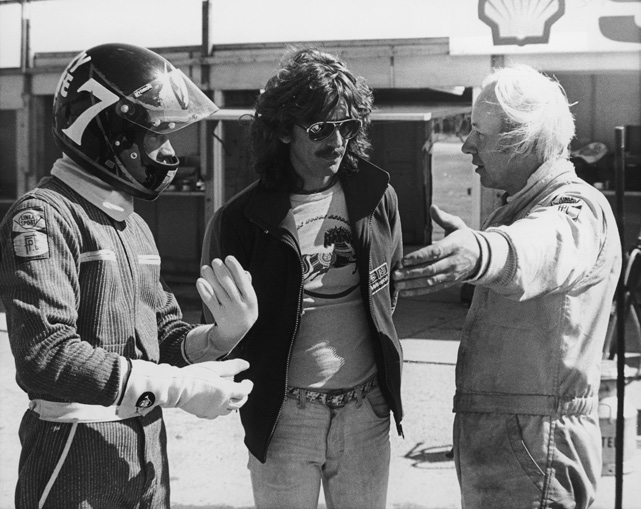 George Harrison chats with British motorbike champion Barry Sheene, who was attempting to race a Formula One car for the first time. Sheene's adviser John Surtees, who successfully made the transition from motorcycle racing to Formula One, also joins the discussion.