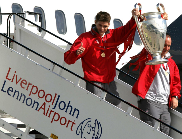 The Liverpool soccer captain Steven Gerrad and manager Benitez carry the Champions League trophy off their plane at John Lennon Airport in Liverpool, England. Liverpool defeated AC Milan in the final a day earlier.