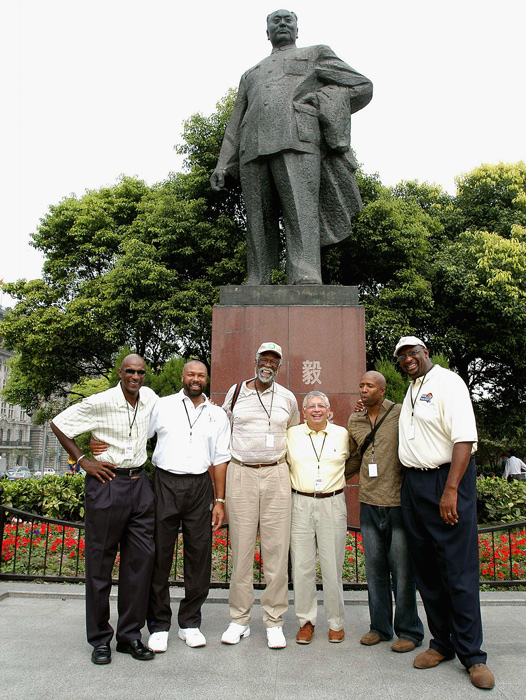 Commissioner David Stern and former players Clyde Drexler, Mel Davis, Russell, Kenny Smith and Bob Lanier pose in front of a statue of Chairman Mao in October 2004 in Shanghai.