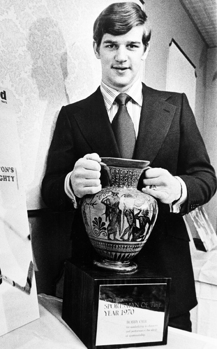 The defenseman holds a Grecian amphora, the Sports Illustrated 1970 Sportsman of the Year award. Orr had led the NHL in scoring and helped the Bruins to the 1970 Stanley Cup title.
