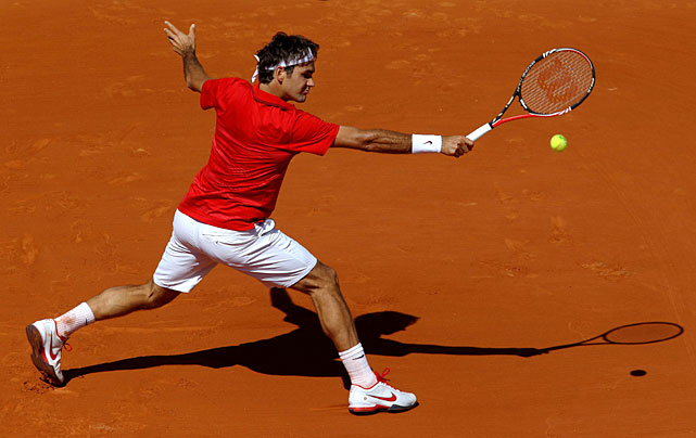 Roger Federer plays a backhand during his first-round match with Spain's Feliciano Lopez of Spain. Federer won 6-3, 6-4, 7-6(3).