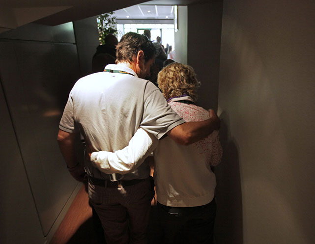 Kim Clijsters is hugged as she leaves the press conference after her second-round loss.