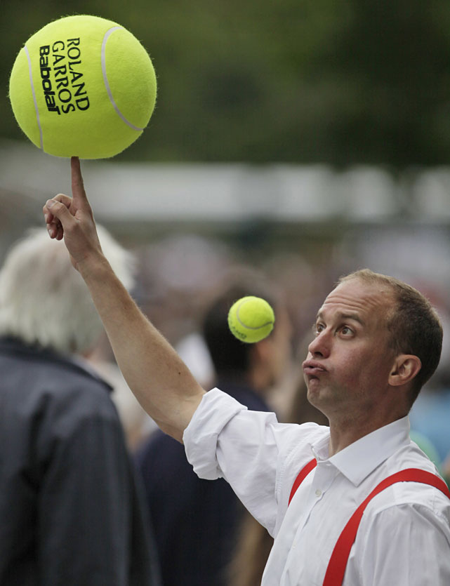 A performer juggles tennis balls as he entertains spectators at the French Open.