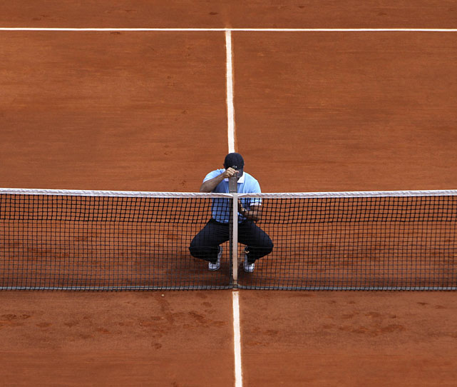 A stadium employee measures the height of the net during a break in the Juan Ignacio Chela-Alejandro Falla match.