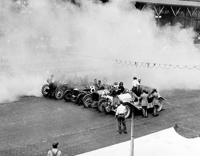 As they prepare at the starting line of the first Indy 500, smoke from oil-burning engines fills the air.