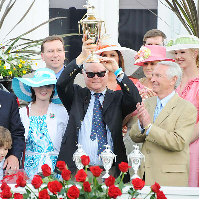 Barry Irwin, owner of Animal Kingdom, lifts the Derby trophy.