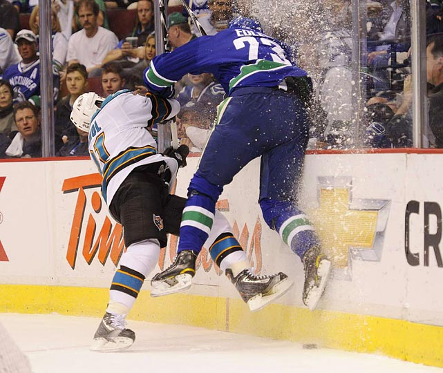 Vancouver Canucks defenseman Alexander Edler (right) lays a vicious hit on San Jose Sharks center Scott Nichol during the Canucks' 7-3 victory in Game 2 of the Western Conference finals.