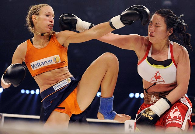 Germany's Christine Theiss (left) strikes first in her women's kick boxing world championship match against South Korea's Lim Su Jeong in Germany on May 28. Theiss would go on to win and defend her world title.