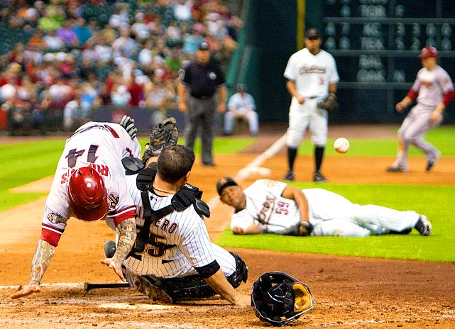Diamondbacks infielder Ryan Roberts (left) collides with Astros catcher Humberto Quintero during the Diamondbacks' 7-6 win on May 27. The home plate collision forced Quintero to leave the game and he was subsequently placed on the DL, becoming the second catcher in as many days to go on the DL following a dustup at home.