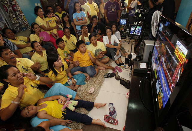 Neighbors and household of Pacquiao, including his daughter Princess (foreground), watch the live broadcast of Saturday's fight at Pacquiao's residence in Laguna province south of Manila.