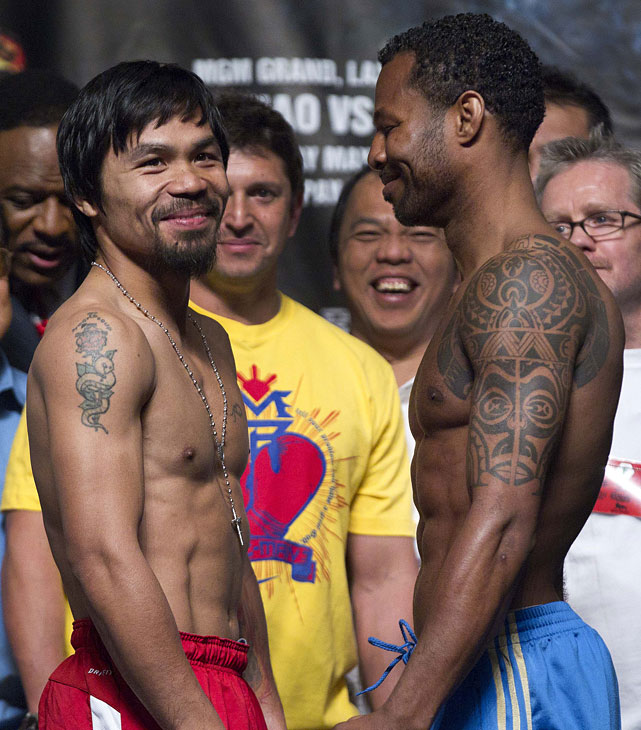 Pacquiao laughs while posing for a face-off photo with Mosley after the weigh-in.