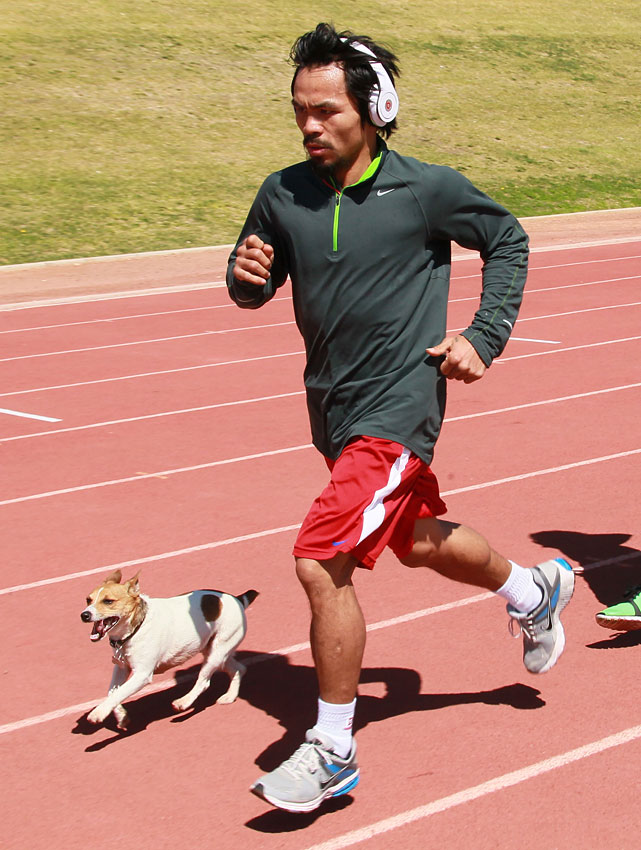 Pacquiao runs with his dog Pacman during a training session at the UNLV track.