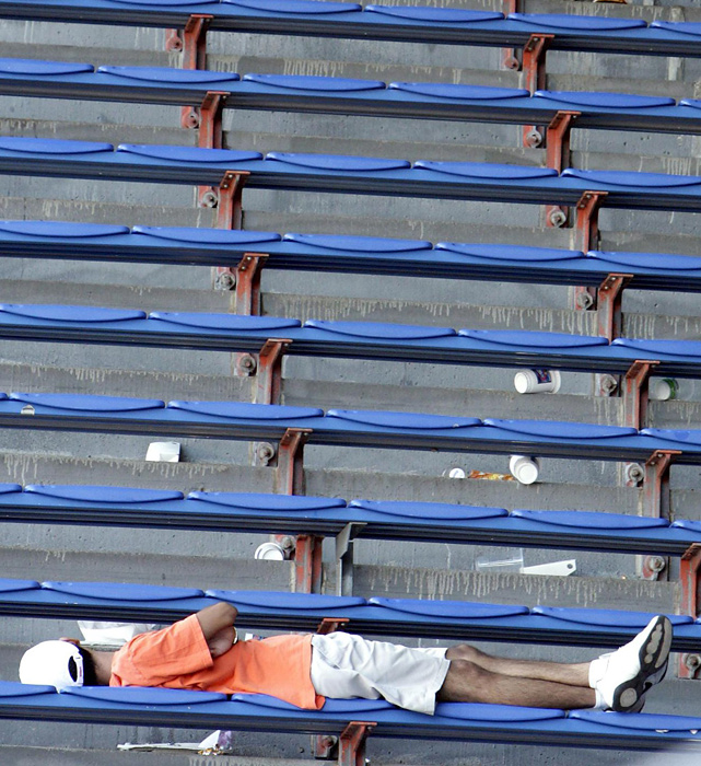 A fan sleeps among empty rows of benches on the Grandstand Court during the 2007 U.S. Open.