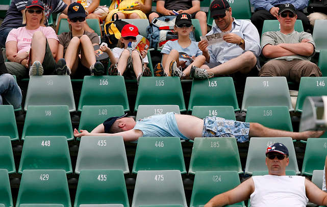 A tennis fan uses five seats to stretch out and nap during a match between   Danai Udomchoke and Juan Carlos Ferrero at the 2007 Australian Open.