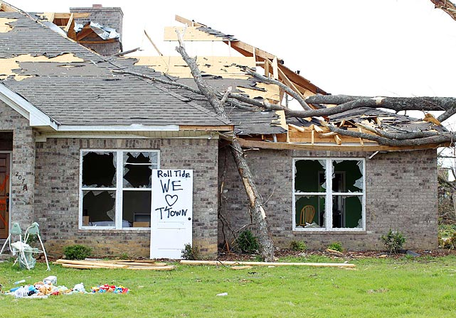 "Alabama football coach Nick Saban is encouraging his team to step forward and help the community in the aftermath. Here, a sign outside a house gutted by the tornado shows the town's signature ""Roll Tide."""