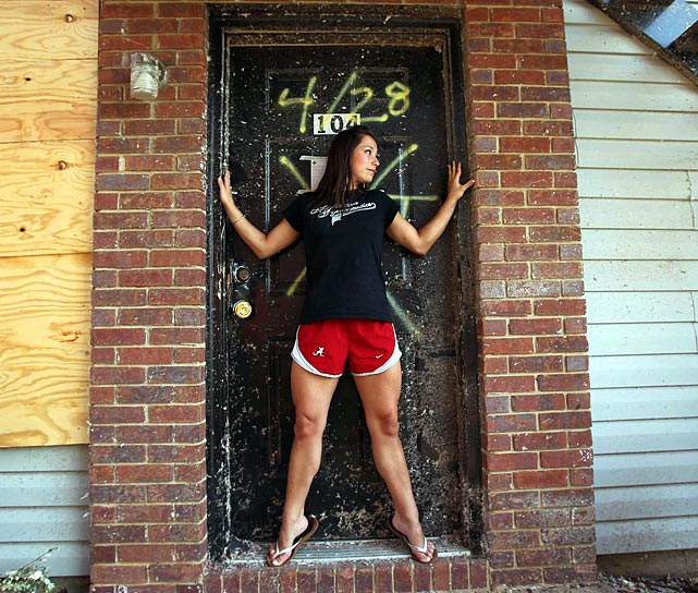 Hoffman poses outside the door frame that helped save her life. Earlier in the day, she was named winner of the Honda Award, given to the top female gymnast in the nation. When the storm hit, she was pummeled by debris as she hid in the door frame.
