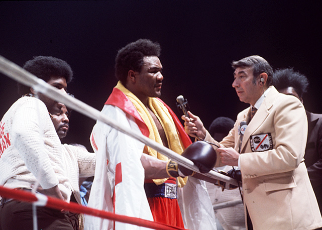 Foreman is interviewed by ABC's Cosell as Don King looks on during an exhibition in Montreal.