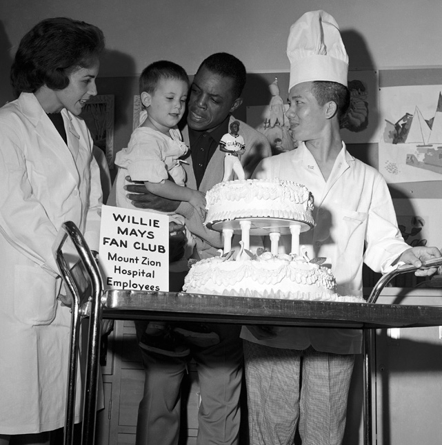 After three days of tests at Mt. Zion Hospital in San Francisco, Mays was pronounced healthy in November 1962. The outfielder checked himself in to make sure his fainting spell two months earlier came from exhaustion and nothing more serious. The hospital's Willie May Fan Club presents him with a cake before he checks out.