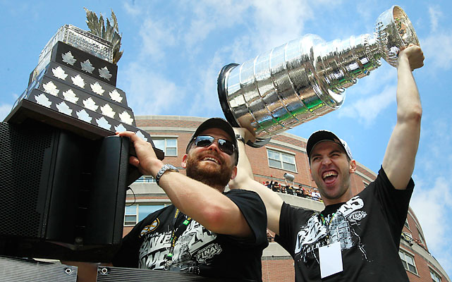Tim Thomas (left) and Zdeno Chara (right) hoist the Conn Smythe and Stanley Cup trophies, respectively.