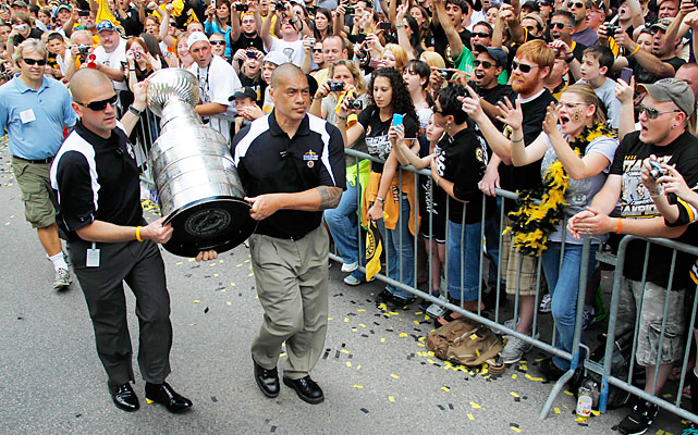 The Stanley Cup is carried through crowds of fans during the victory celebration.