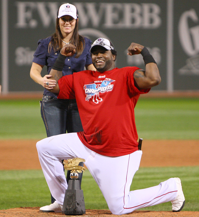 Ortiz flexes his muscle with his wife, Tiffany, behind him after the Red Sox took down the Cleveland Indians in seven games during the 2007 ALCS.