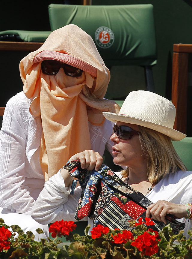 Two spectators shield themselves from the sun as they watch the Rafael Nadal-Andy Murray match at Roland Garros.