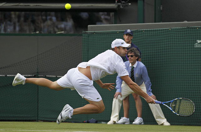 Andy Roddick tumbles to the grass during his first-round match with Germany's Andreas Beck.