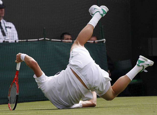 Tomas Berdych of the Czech Republic tumbles to the ground during his match against France's Julien Benneteau.
