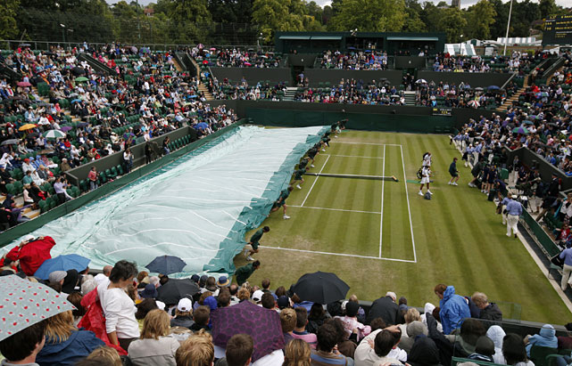 Covers are pulled over a court as rain stops play at Wimbledon.