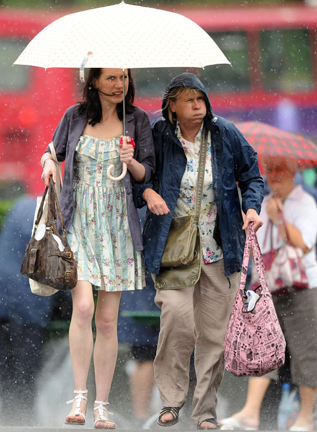 Tennis fans take cover as rain falls at Wimbledon.