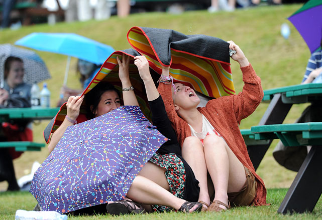 Tennis fans take cover as rain falls on Tuesday at Wimbledon.
