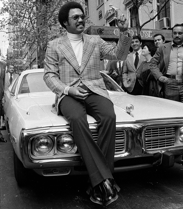Reggie Jackson sitting on the hood of his car.