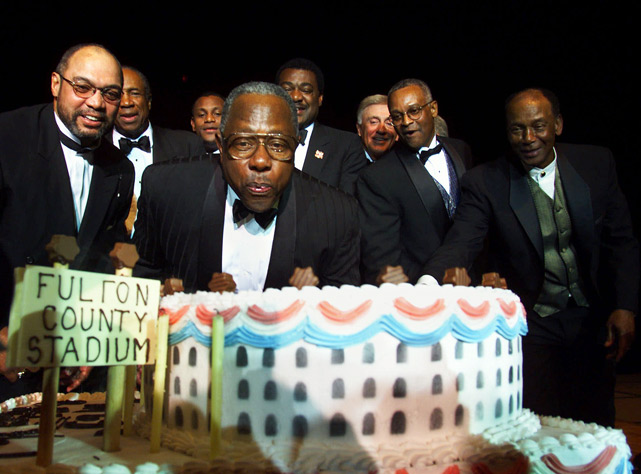 Former career home run leader Hank Aaron (center) is joined by baseball greats Reggie Jackson, Frank Robinson, Sammy Sosa, Don Baylor, Phil Niekro, Sonny Jackson and Ernie Banks as he blows out the candles on his 65th birthday cake.