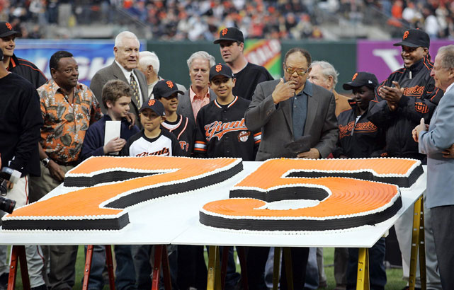 Former Giants great Willie Mays (fifth from right) samples his massive birthday cake.