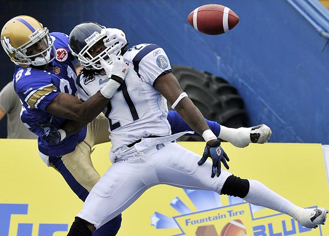They're playing football somewhere. Defensive back Lin-J Shell of the CFL's Toronto Argonauts gets roughed up by Winnipeg Blue Bombers wide receiver Cory Watson after Shell stepped in front of a pass.