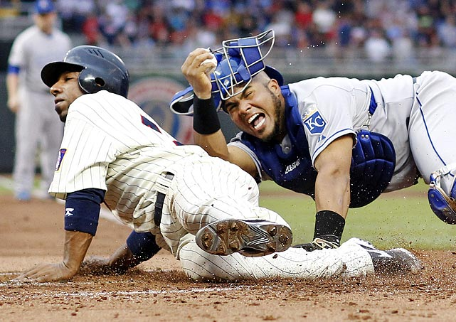 Minnesota Twins infielder Alex Casilla gets tagged out by Kansas City Royals catcher Brayan Pena in a bang-bang play. Casilla was attempting to score from third on a sacrifice fly.