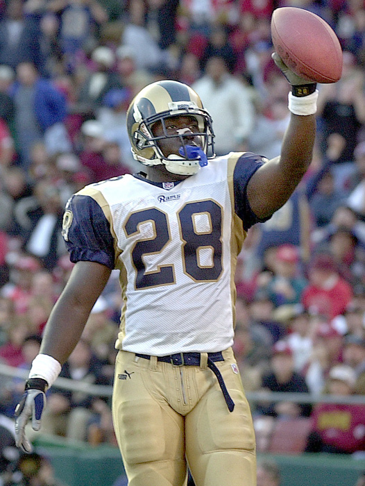 """Teamed with head coach Dick Vermeil and offensive coordinator Mike Martz, Faulk made an immediate impact in St. Louis and was a catalyst for """"The Greatest Show on Turf."""" He gained an NFL-record 2,249 yards from scrimmage in leading the Rams to a 13-3 record."""
