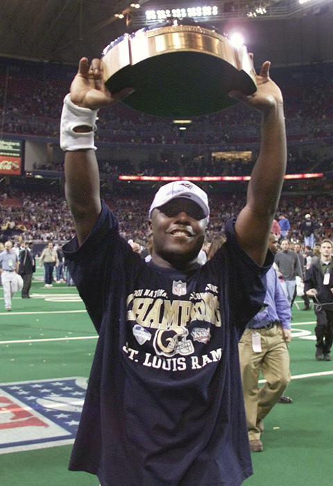 In 2001, Faulk led the Rams back to the championship, where they lost to the Patriots. In this photo, Faulk holds up the George S. Halas Trophy after the Rams beat the Eagles in the NFC Championship game.
