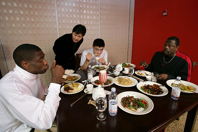 Yao Ming having lunch with Dikembe Mutombo and Patrick Ewing as his mother looks on at Yao's Restaurant & Bar.
