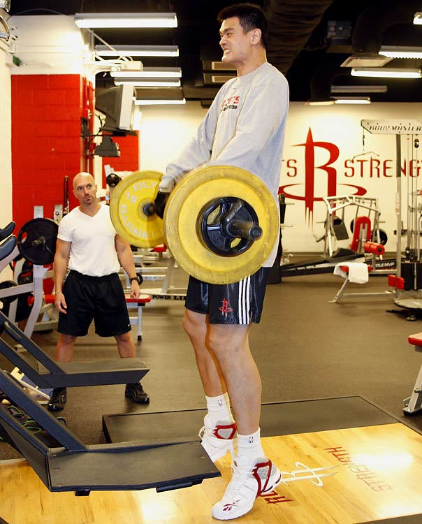 Yao Ming lifting weights during a workout in the gym at Toyota Center in Houston.
