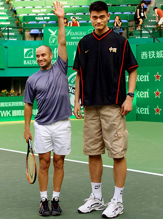 Andre Agassi jokes around next to 7'4'' Yao Ming during a tennis charity promotion in Shanghai.