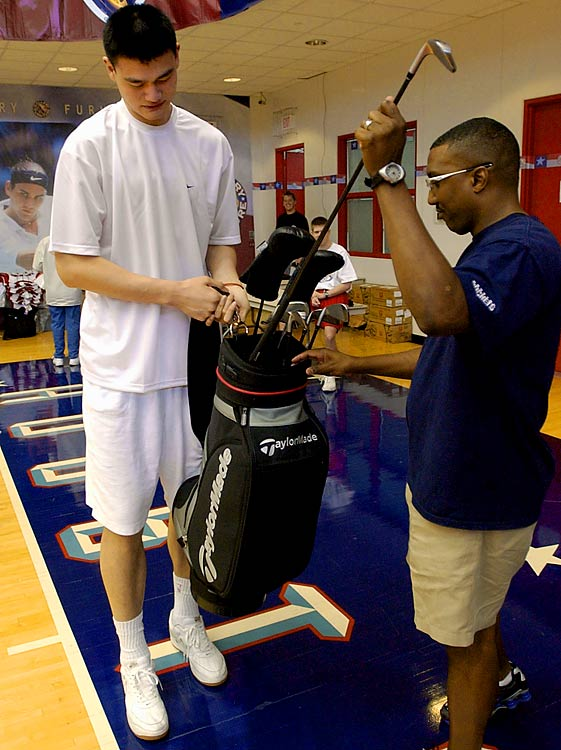 Rockets trainer Keith Jones helps Yao Ming with his golf clubs at the team's practice facility.