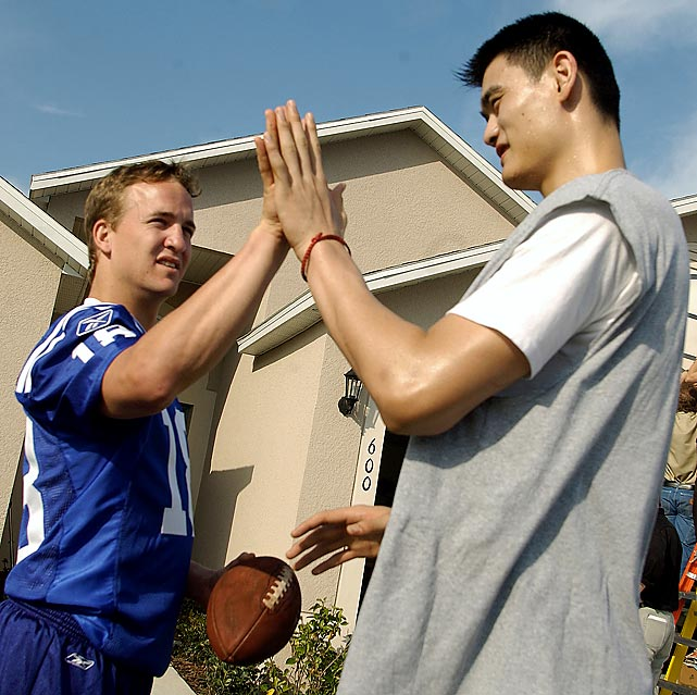 Yao Ming and Peyton Manning high-five each other between takes during shooting for a Gatorade commercial in Orlando.