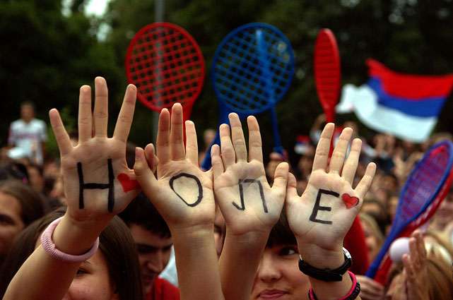 "People have Novak Djokovic's nickname ""NOLE"" written in Cyrillic letters on their palms as they celebrate his homecoming in Belgrade."