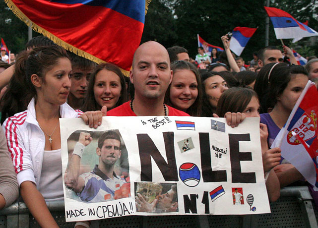 A fan holds a sign celebrating Novak Djokovic's rise to the No. 1 ranking.