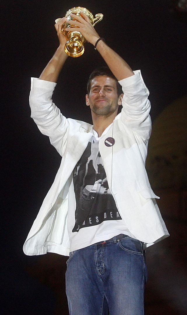Novak Djokovic hoists the Wimbledon trophy at Monday's homecoming.