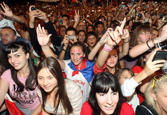 People celebrate and wave Serbian flags at a welcoming ceremony for Novak Djokovic.
