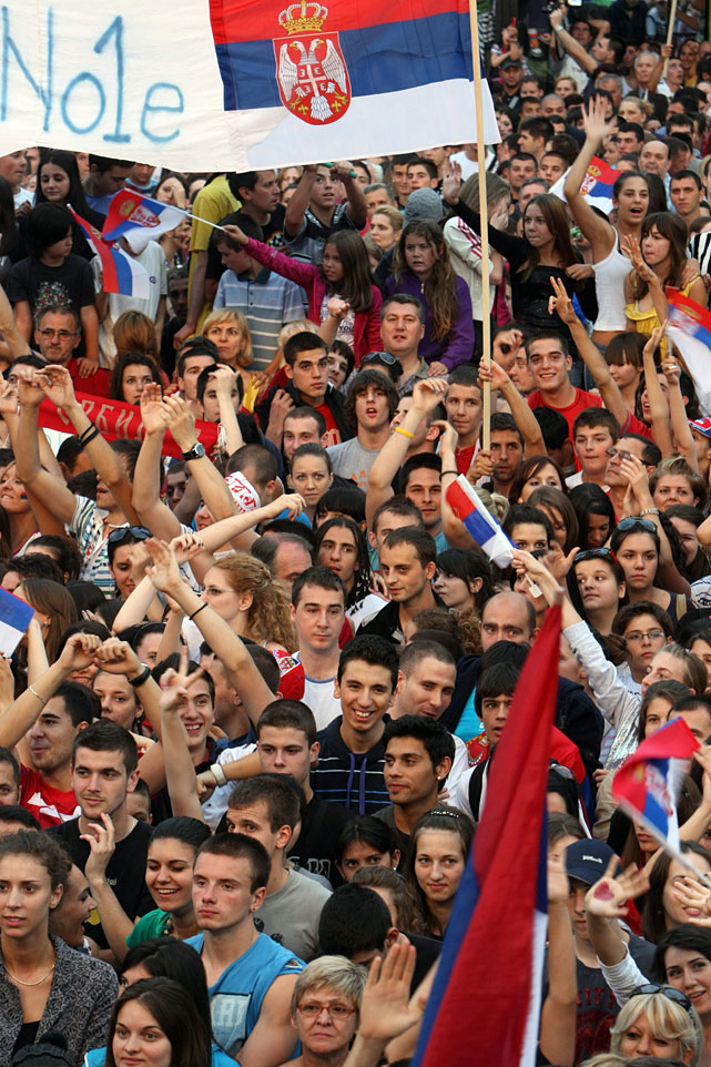 People celebrate and wave Serbian flags at Novak Djokovic's homecoming celebration on Monday.