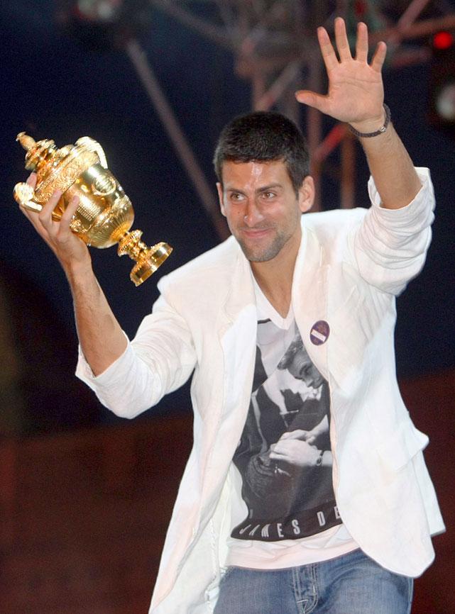Novak Djokovic jubilates with the Wimbledon trophy at his homecoming.