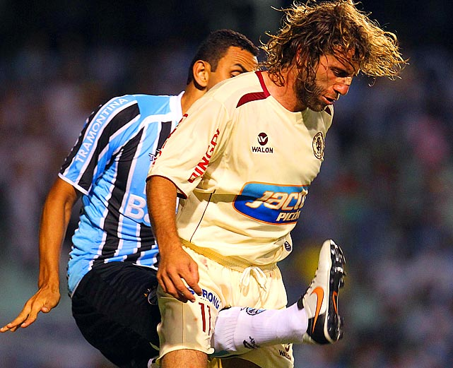 Peru's Leon de Huanuco gets a not-too-friendly from Rafael Marques's foot during a Copa Libertadores soccer game in Porto Alegre, Brazil.